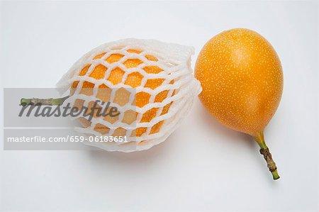 Two granadillas, one in a net packaging