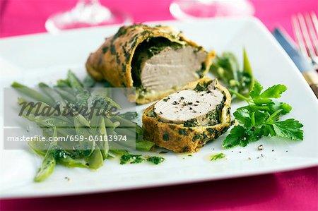 Un filet de porc enveloppé de pâte avec les herbes et les mangetouts