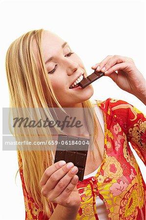 Une jeune femme de mordre un morceau de chocolat noir