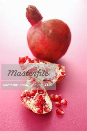 Ganze Granatapfel und Stücke von Granatapfel
