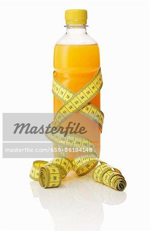 Une bouteille de jus d'orange avec un ruban à mesurer