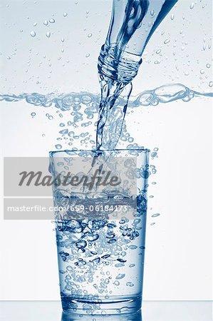 Versez l'eau d'une bouteille dans un verre