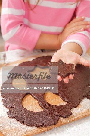 Ein Mädchen hält einen Ausschnitt sternförmige Keks