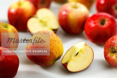 Pommes rouges, entiers, coupés en deux et tranché