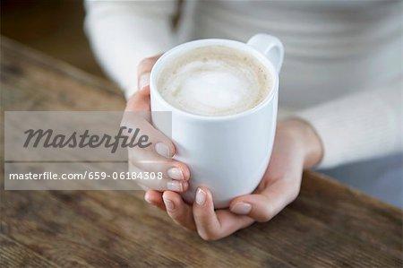 Une paire de mains tenant une tasse de cappuccio