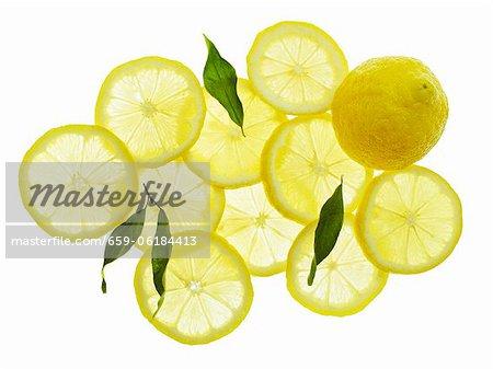 Eine ganze Zitrone, Zitronenscheiben und Blätter