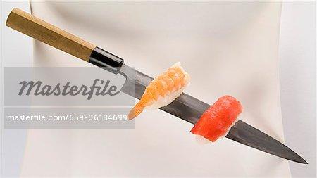 Nigiri saumon et crevettes sur un couteau à sushi