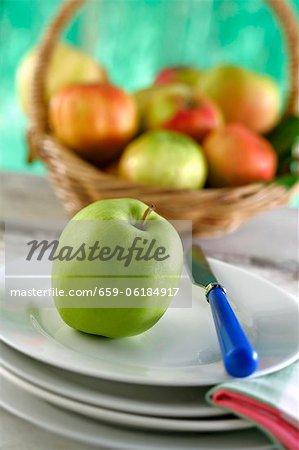 Une pomme sur plaque devant un panier de fruits