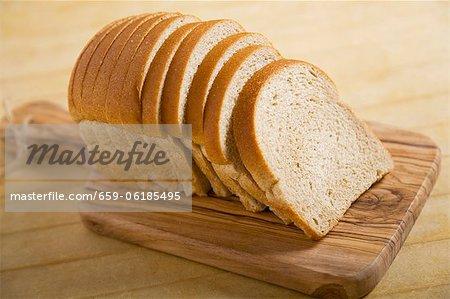 Miche de pain de blé en tranches sur une planche à découper