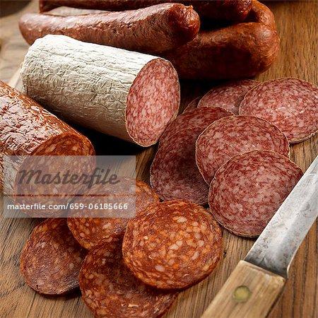 Salami en tranches et entier sur une planche à découper avec couteau