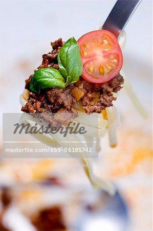 Linguine avec une sauce de viande hachée, de tomates et de basilic sur une fourche