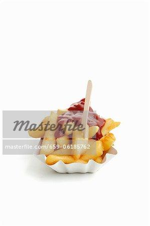 Frites et ketchup sur une assiette en papier à emporter