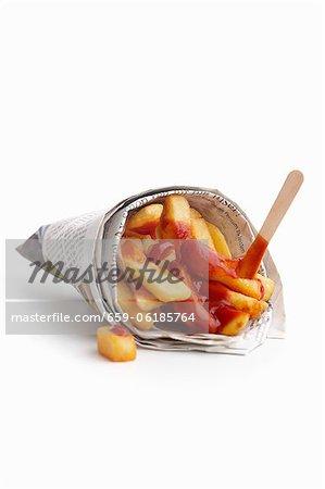 Frites avec du ketchup enveloppés dans journal