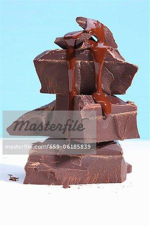 Chocolat liquide dégoulinant d'une pile de morceaux de chocolat