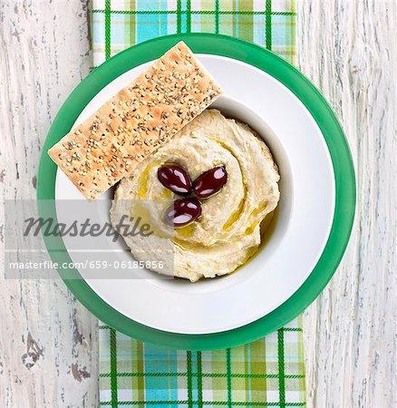 Hoummos avec huile d'Olive et des Olives dans un bol avec sésame Graines pain plat