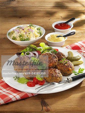 Meatballs with potato salad, mustard and ketchup