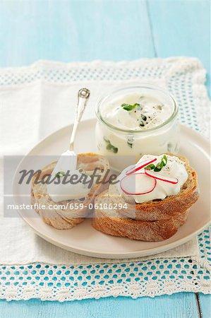 Scheiben Brot belegt mit Schnittlauch-Quark und Radieschen