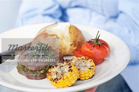 Une personne titulaire d'une plaque de médaillons de boeuf grillé, pommes de terre veste et tomates grillées et du maïs en épi
