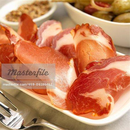 Tranches de séché salé longe de porc espagnol sur un plateau ; Poivrons et Olives