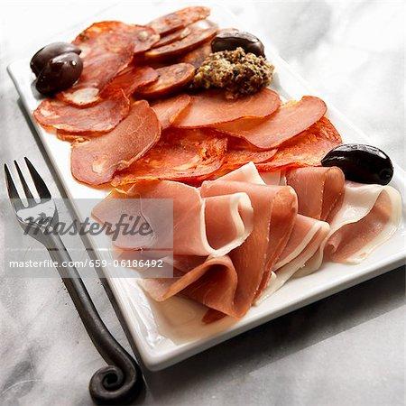 Assiette de tapas avec jambon Serrano, Pamploma, Lomo, Soria, saucisses piquantes et Olives noires