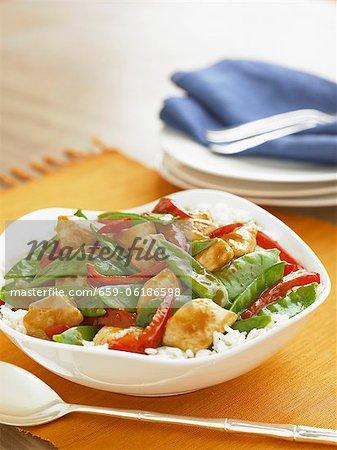 Poulet sauté avec des pois mange-tout et poivrons rouges sur le riz dans un bol de service