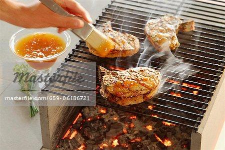 Côtelettes sur le gril est brossé avec sauce aux abricots