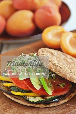 Sandwich aux légumes avec des aubergines, courgettes, poivrons jaunes, tomate et avocat sur un plat rond Roll
