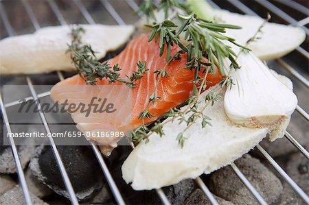 Ein Lachsfilet und Scheiben Brot auf ein Barbecue mit Trauben von Kräutern