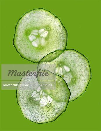 Trois tranches de concombre sur une surface verte