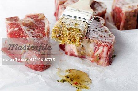 Côtelettes d'agneau crue badigeonner de Marinade et brosse