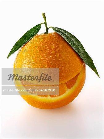 Eine Orange mit Blättern und ein Stück aus ihm heraus genommen