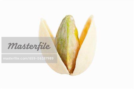Eine geöffnete, geröstete Pistazien vor einem weißen Hintergrund