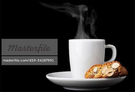 Biscotti (biscuits aux amandes italiennes) et une tasse d'expresso sur fond noir