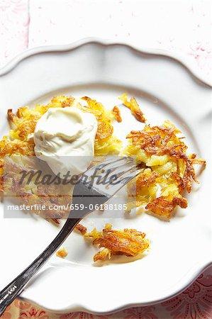 Pommes de terre rösti (rissolées) avec la crème sur une assiette avec une fourchette