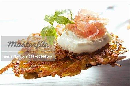 Pommes de terre rösti (hash brown) avec la crème sure et jambon fumé