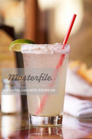 Margarita dans un verre avec une jante salée et une paille rouge