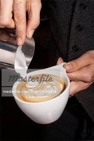 Person Pouring Cream into a Cappuccino