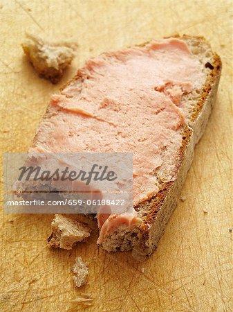 Une tranche de pain garnie de teewurst avec une morsure souscrite