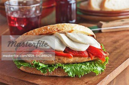Gegrillte Hähnchenbrust-Sandwich mit geröstete Paprika, Mozzarella-Käse und Salat gegrillte toskanischen Boule-Brotaufstrich