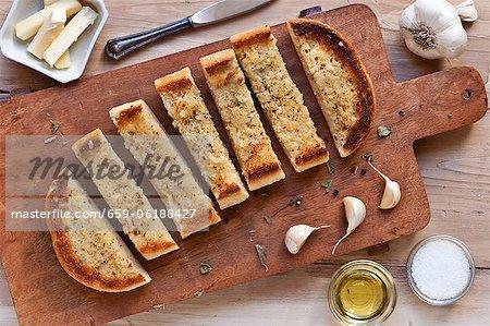 Knoblauch-Brot in Scheiben geschnitten auf einem Schneidebrett aus Holz; Von oben; Zutaten für Knoblauchbrot