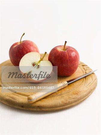 Rote Äpfel, ganze und halbierte, auf einem Holztisch