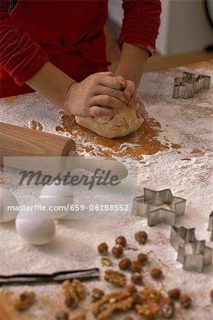 Un enfant de pétrir la pâte à biscuit sur une surface de travail enfarinée