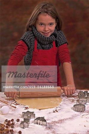 Ein Mädchen, Roll-out Biskuitteiges mit einem Nudelholz auf einer Arbeitsfläche