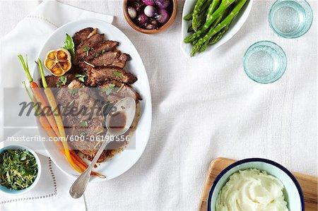 Poitrine de boeuf avec herbes, asperges, pommes de terre et oignons grelots