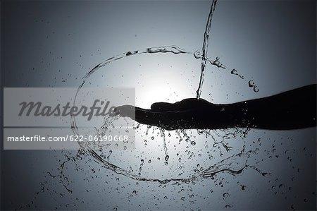 Main de l'homme et les projections d'eau