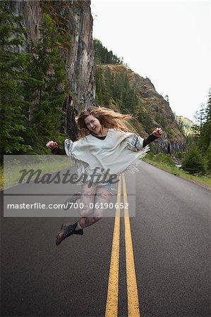 Jeune femme sautant au milieu de la route