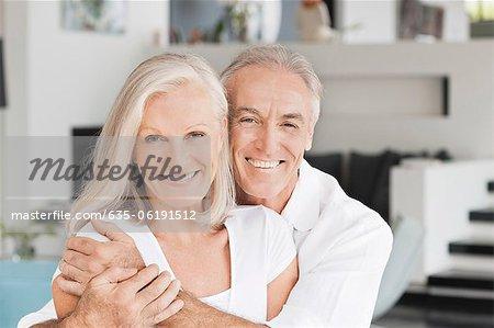 Portrait de sourire couple s'enlaçant dans le salon