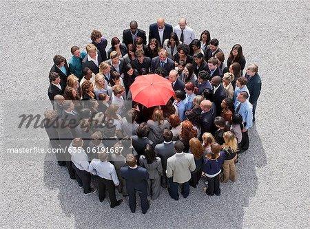 Parapluie au centre du cercle formé par les gens d'affaires