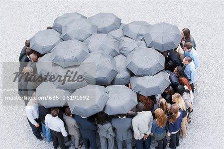 Cercle formé de gens d'affaires avec des parapluies