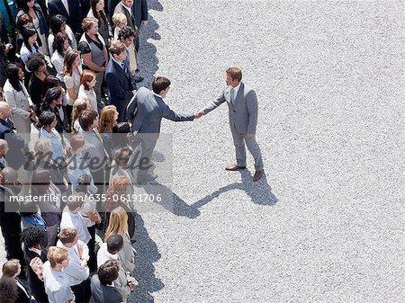 Businessman shaking man's hand in crowd